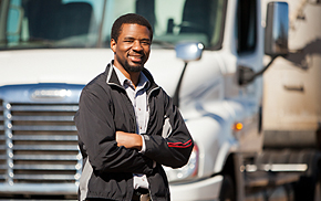 man standing in front of a white commercial motor vehicle