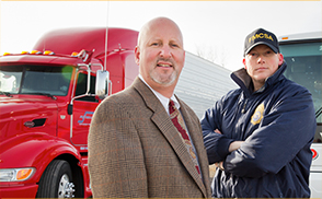 man in suit and a FMCSA state official standing in front of a red commercial motor vehicle